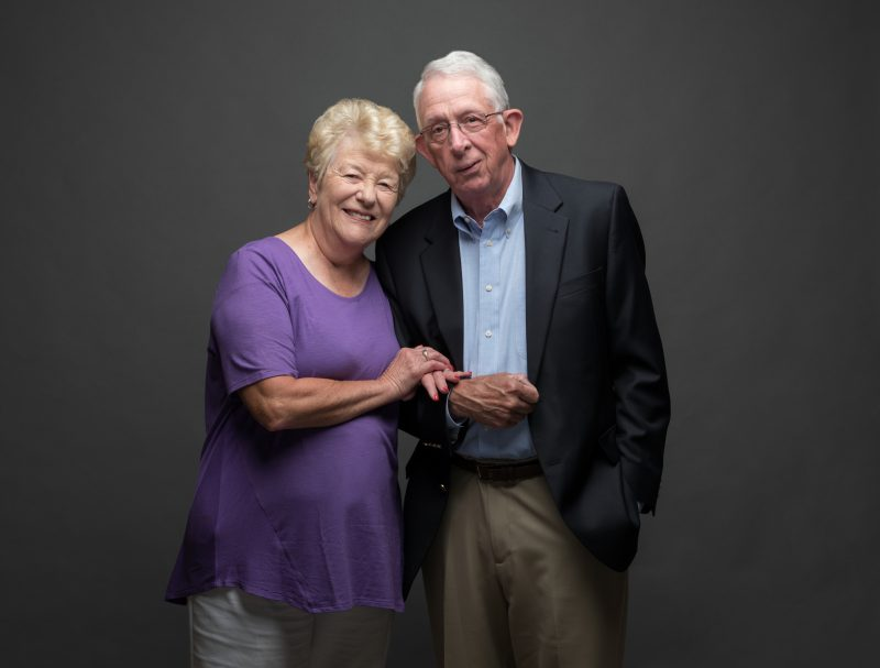 Married couple Sharon and Tom Kennedy stand close together, in front of a grey backdrop.
